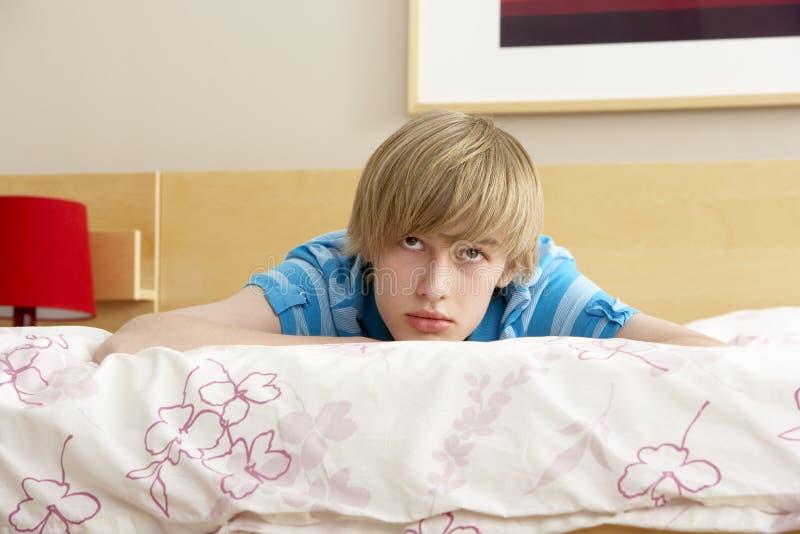 看起来哀伤少年的卧室男孩 免版税库存图片