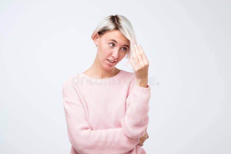看起来哀伤的不快乐的担心的紧张的翻倒的女孩审查她在不良状态头发损坏了 库存图片