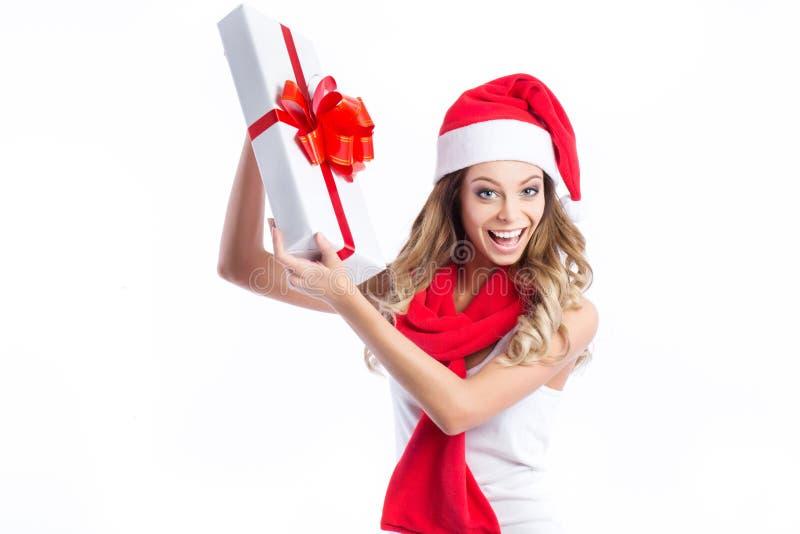 看起来圣诞老人的帽子的年轻愉快的妇女斜向一边显示圣诞节礼物 免版税图库摄影