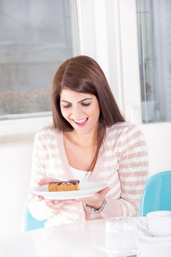 看起来在桌上的俏丽的妇女甜点心与微笑 库存图片