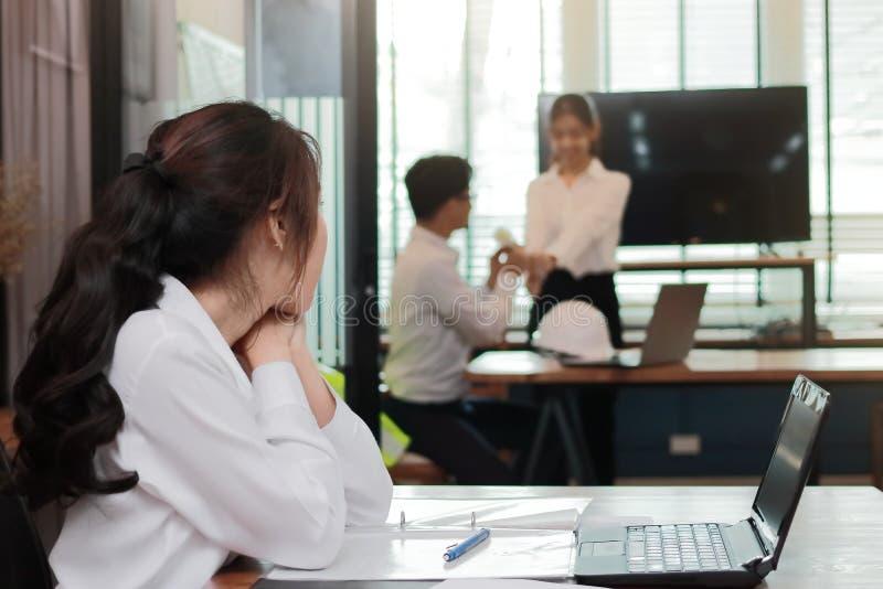 看起来在爱的羡慕恼怒的亚裔女商人富感情的夫妇在办公室 嫉妒和妒嫉在朋友关系 免版税库存图片