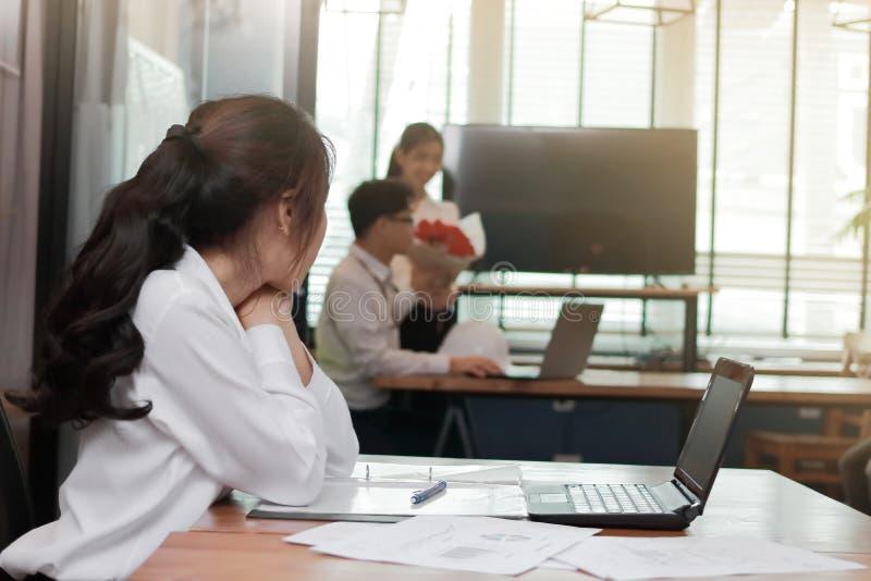 看起来在爱的羡慕恼怒的亚裔女商人富感情的夫妇在有阳光作用的办公室 嫉妒和妒嫉在朋友 免版税库存图片