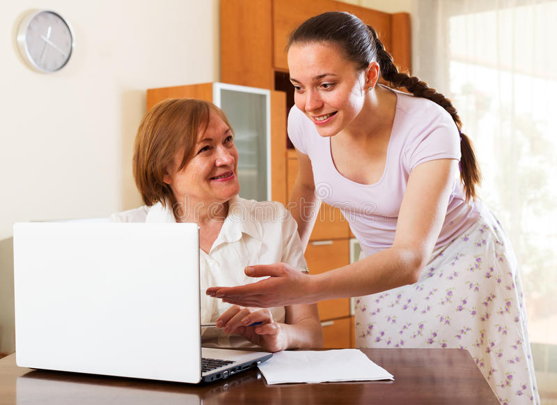 看起来在膝上型计算机的微笑的妇女财政文件 免版税库存图片