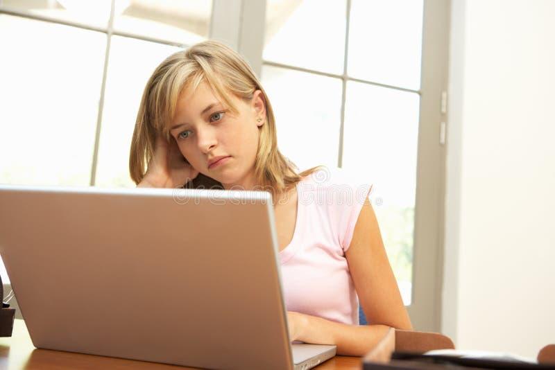 看起来女孩家庭的膝上型计算机少年&# 免版税图库摄影