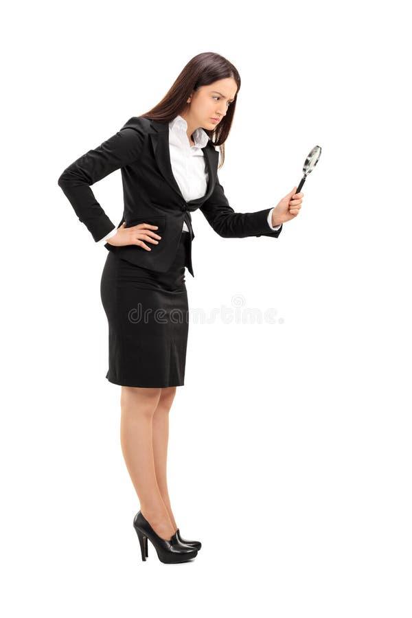 看起来女实业家的玻璃扩大化 免版税图库摄影