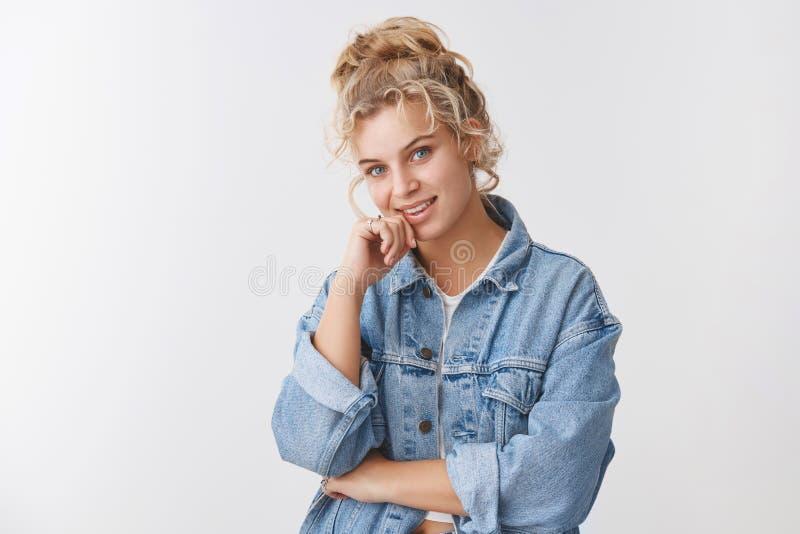 看起来好奇照相机微笑的时兴的时髦的欧洲白肤金发的女孩被吸引听有趣建议咧嘴 免版税图库摄影