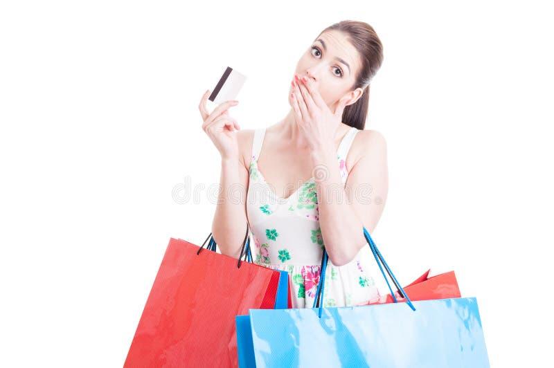 看起来妇女的顾客惊奇拿着信用或转账卡 库存图片