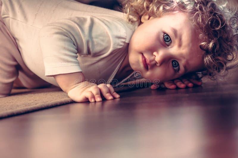 看起来害怕的孩子掩藏在床下在孩子屋子里和惊吓 库存图片