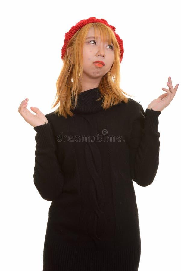 看起来年轻体贴的亚裔的妇女与被举的胳膊混淆 库存图片