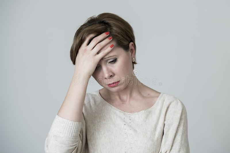 看起来年轻俏丽和哀伤的红色头发的妇女担心的和沮丧的哭泣的和遭受的头疼和偏头痛痛苦和消沉 免版税图库摄影