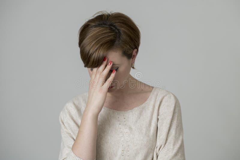 看起来年轻俏丽和哀伤的红色头发的妇女担心的和沮丧的哭泣的和遭受的头疼和偏头痛痛苦和消沉 免版税库存图片