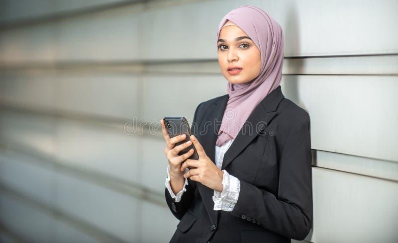 看起来年轻女性回教的企业家严肃,拿着她的智能手机 免版税库存图片