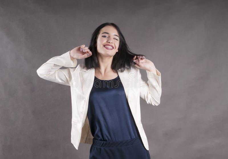 看起来快乐的阳表示的年轻美丽的愉快的女实业家支撑深色的演播室 库存图片