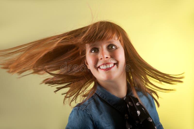看起来快乐的黄色背景的红头发人女孩 免版税图库摄影