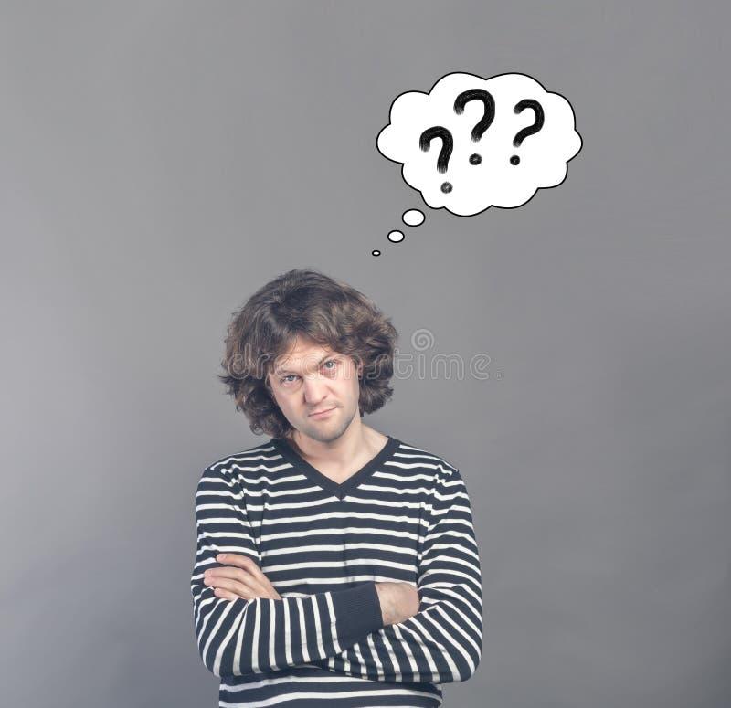 看起来怀疑的人可疑和可疑与想法拉长的云彩与三个问号的在它 某一不赞成 免版税图库摄影