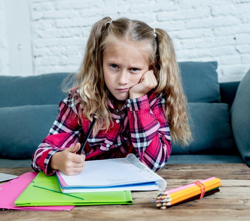 看起来恼怒不耐烦的逗人喜爱的甜哀伤和被淹没的金发小学女孩和疲乏在与家庭作业和学习的重音 图库摄影