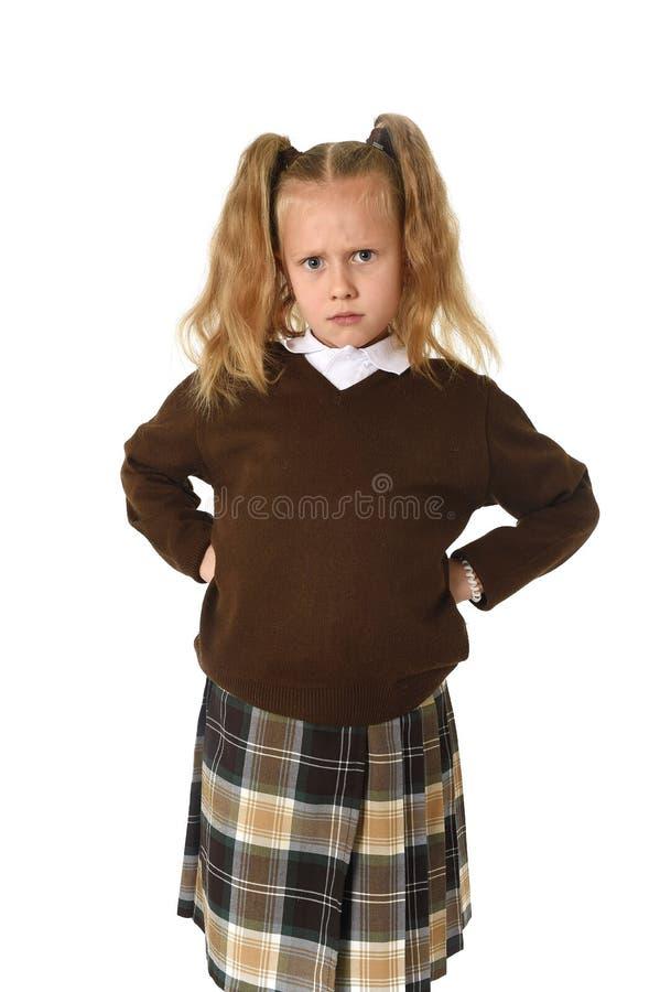 看起来恼怒的翻倒的猪尾和校服的甜年轻女小学生被挫败和不快乐 库存图片