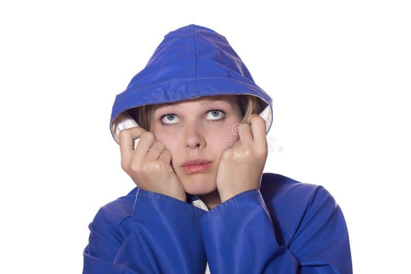 看起来悲观的雨妇女的蓝色外套 免版税库存照片