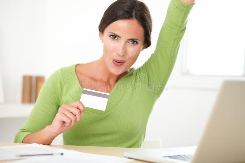 看起来愉快的可爱的女性快乐在她的书桌上 库存图片