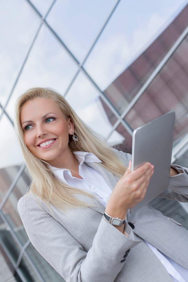 看起来愉快的女实业家去,当拿着数字式片剂反对办公楼时 库存照片