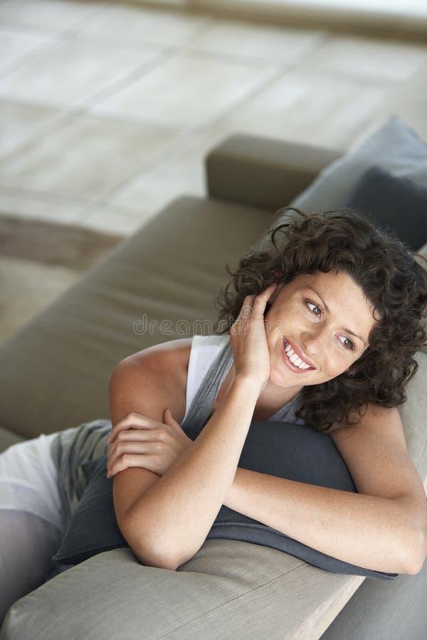 看起来愉快的少妇去,当放松在长沙发时 免版税库存照片