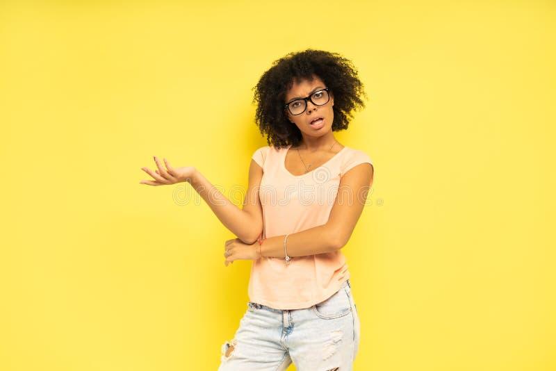 看起来愉快的非裔美国人的妇女惊奇在黄色背景 免版税库存图片