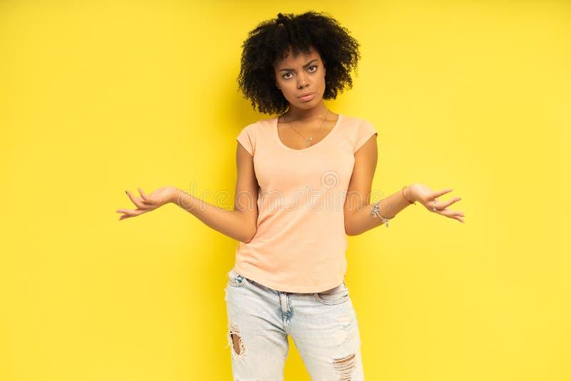 看起来愉快的非裔美国人的妇女惊奇在黄色背景 库存照片