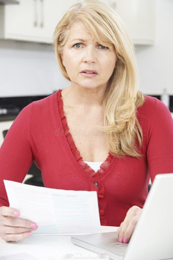 看起来担心的成熟的妇女在家回顾财务 库存图片