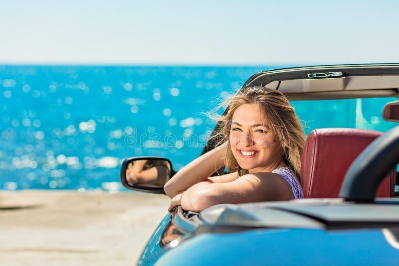看起来敞篷车顶面的汽车的美丽的白肤金发的微笑的少妇斜向一边,当停放在海洋江边附近时 免版税库存图片