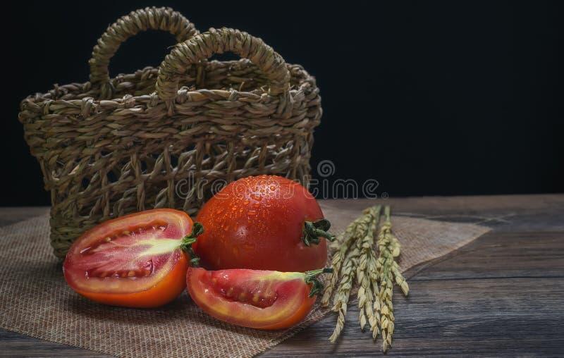 看起来有吸引力在木地板和背景篮子上的红色蕃茄 库存图片