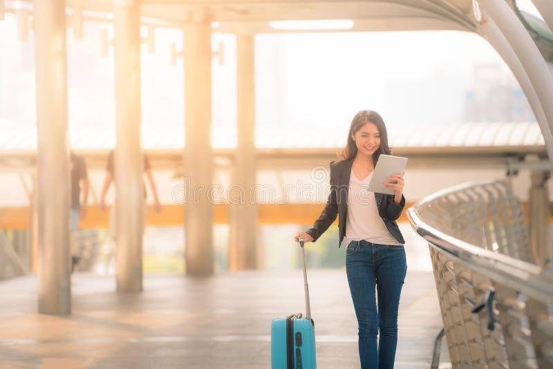 看起来有蓝色旅行包的女商人画象数字片剂在走道 葡萄酒口气 免版税图库摄影