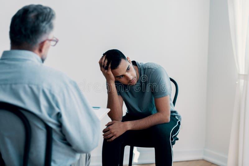 看起来沮丧的少年去,当谈话与他的治疗师时 免版税库存照片