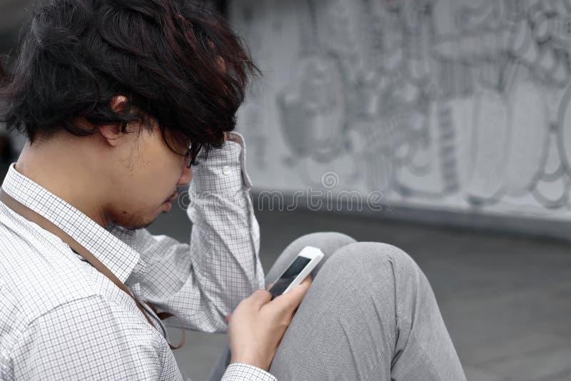 看起来流动巧妙的电话的担心的沮丧的年轻亚洲商人 忧虑企业概念 免版税图库摄影
