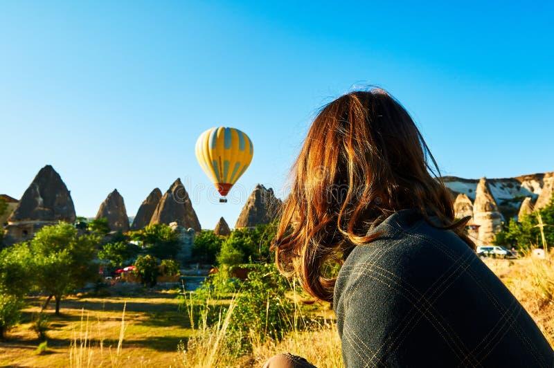 看起来热空气的妇女迅速增加在蓝色绿松石天空在卡帕多细亚土耳其在日出 免版税库存照片