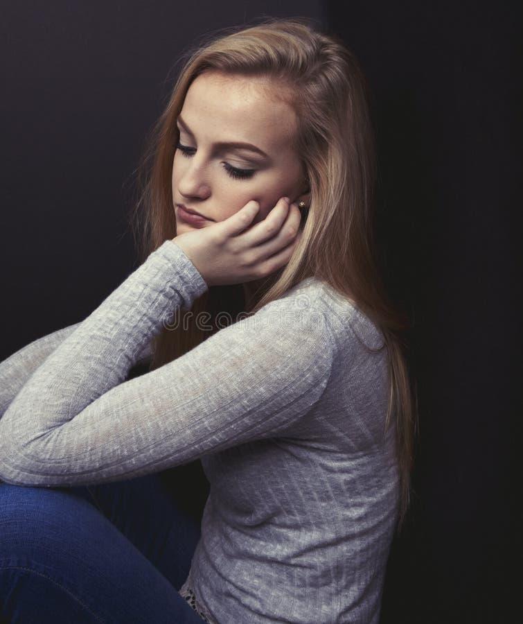 看起来白肤金发的十几岁的女孩哀伤休息她的在她的手上的头 库存照片