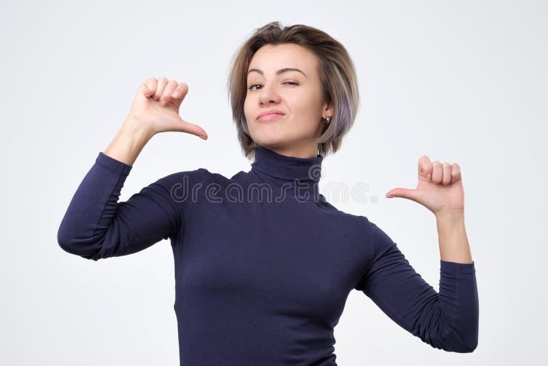 看起来的妇女确信与在面孔的微笑,指向与是的手指感到骄傲 图库摄影