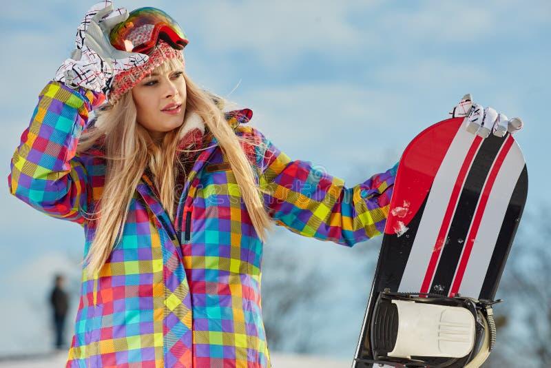 看起来的少妇去,当拿着在雪时的雪板 免版税图库摄影