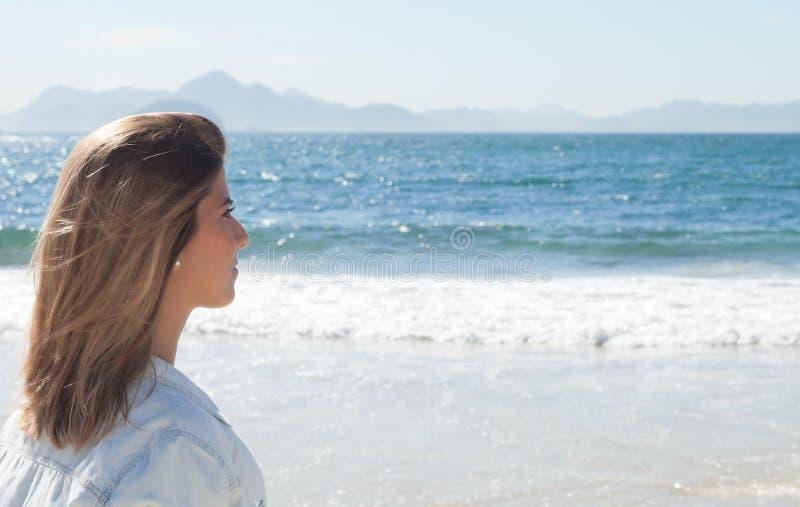 看起来的海滩的白肤金发的妇女周道对海洋 免版税库存图片