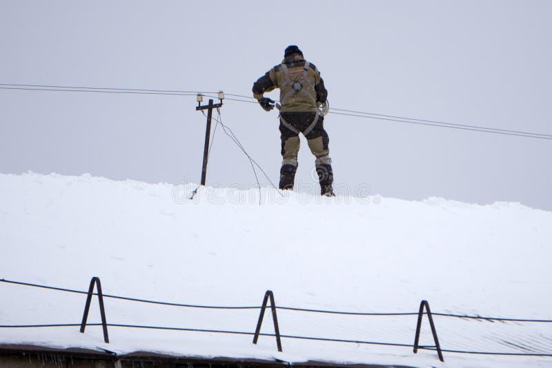 看起来的电工站立在顶面屋顶和去,当认为时 拿着安全帽的建筑工人背面图看a 图库摄影