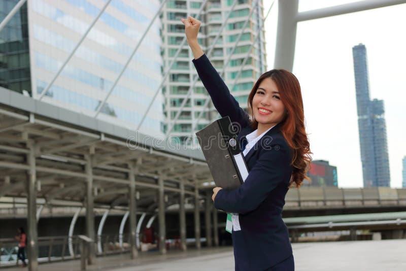 看起来确信和微笑在城市背景中的快乐的亚裔女实业家画象  成功的企业概念 免版税库存照片