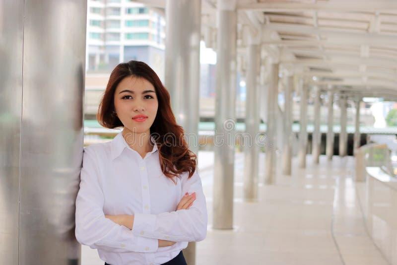 看起来确信摆在外面在都市背景的可爱的年轻亚裔女实业家画象  领导妇女概念 免版税库存照片