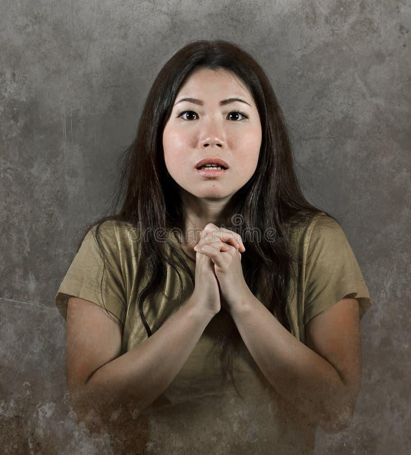 看起来祈祷的手势的年轻美丽的哀伤和担心的亚裔韩国妇女被注重的和绝望遭受的痛苦和expe 免版税库存图片