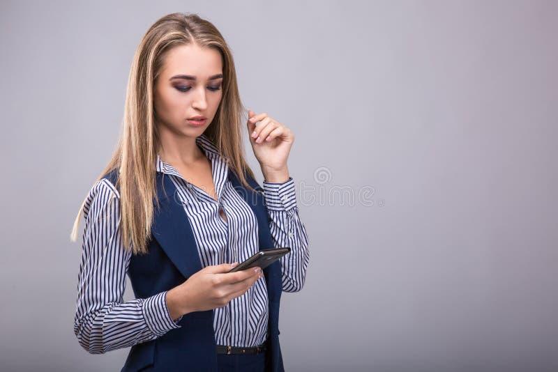 看起来移动电话妇女的商业 免版税库存照片