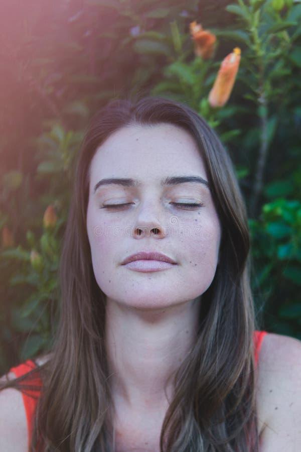 看起来美丽的妇女放松和平静与她的眼睛关闭了 免版税图库摄影