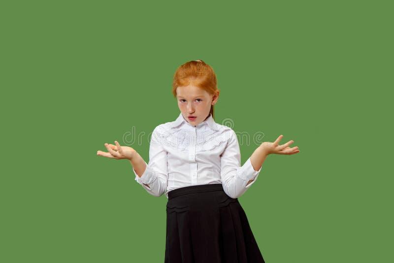 看起来美丽的青少年的女孩惊奇和迷惑隔绝在绿色 免版税库存图片