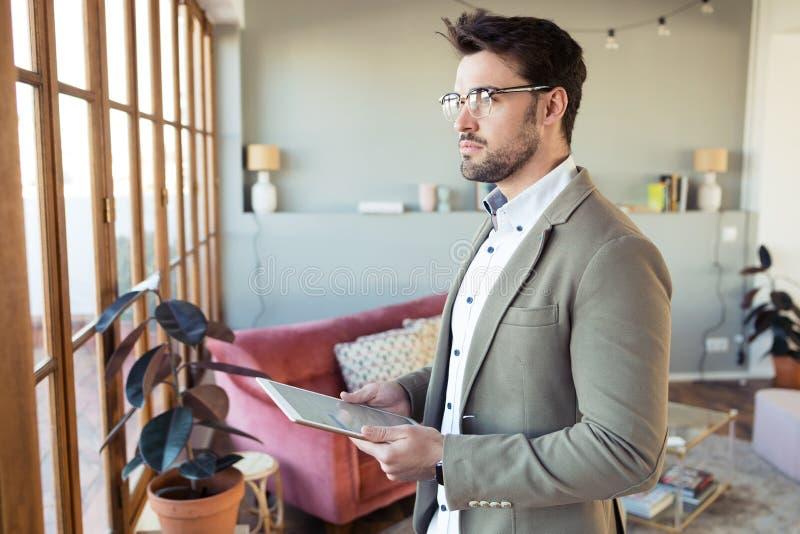 看起来英俊的年轻的商人斜向一边,当使用他的数字片剂在办公室时大厅里  免版税图库摄影