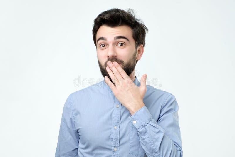 看起来蓝色衬衣覆盖物嘴的Ood西班牙年轻人用手 图库摄影