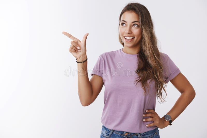 看起来被启发的发笑指向的梦想的可爱的现代年轻女人看起来惊奇的左上部角落,广泛地微笑 免版税库存照片