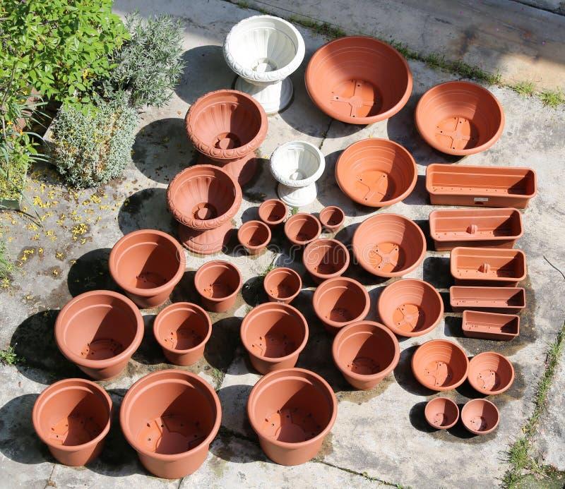 看起来象赤土陶器在卖花人的待售的塑料花瓶 库存照片