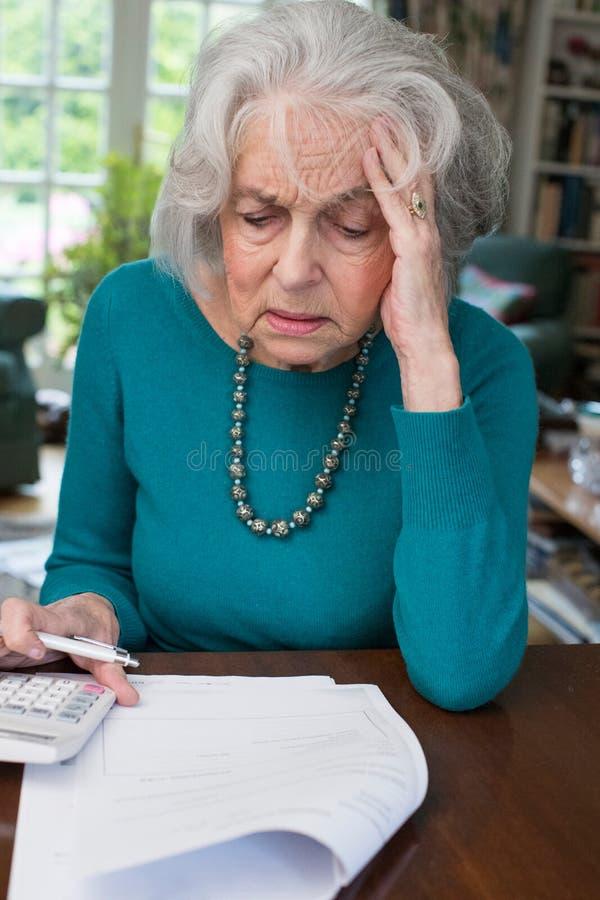 看起来资深的妇女审阅票据和担心 免版税库存照片